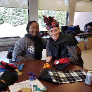 Two CCCU staff members making winter hats