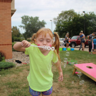 Young girl blowing bubbles at Kids Day